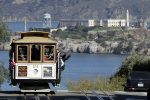 Cable Car riders take pictures looking toward Lombard Street as they ride up Hyde Street with Alcatraz Island in the background, Tuesday, March 11, 2014, in San Francisco. (AP Photo/Jeff Chiu)